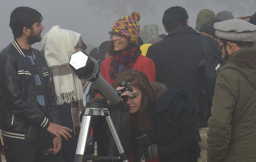 People watching the solar eclipse through a telescope in Islamabad