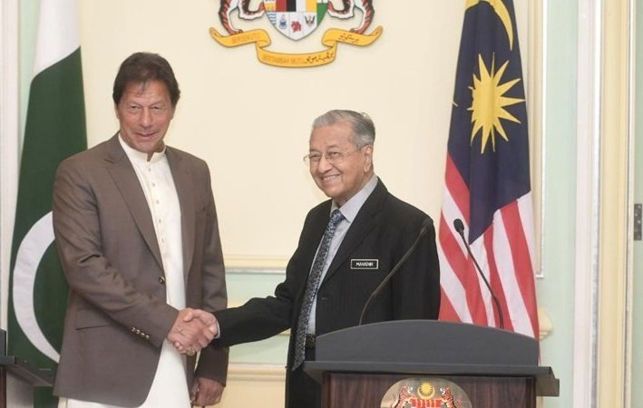 Prime Minister Imran Khan shakes hands with Malaysian Prime Minister Mahathir Mohamad in Putrajaya